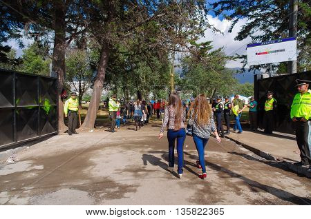 QUITO, ECUADOR - JULY 7, 2015: Two girls entering to the place to hear pope Francisco mass, police guarding in the enter doors.