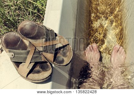 Man feet refreshing in a cool irrigation canal during the hottest day hours Vegas Altas del Guadiana Spain