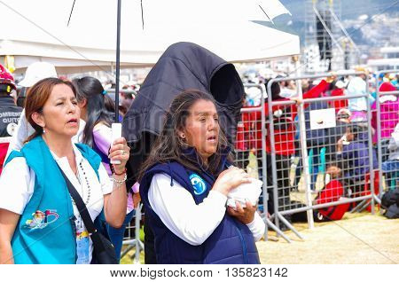 QUITO, ECUADOR - JULY 7, 2015: Two mature womans praying and singing at pope Franciscco mass on Ecuador, sunny day.