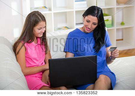 Happy mother and daughter shopping online using laptop and credit card sitting on the couch or sofa