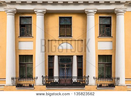 Several windows columns and balconies in a row on facade of urban apartment building front view St. Petersburg Russia