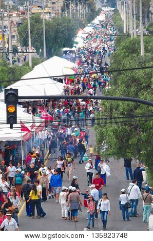 QUITO, ECUADOR - JULY 7, 2015: Large avenue at the city crowded because of pope Francisco mass, redlight and cable son the posts.