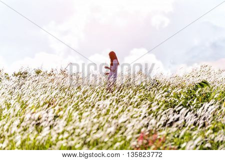 Young woman standing on a wheat field on sunset