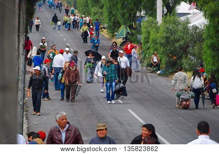 QUITO, ECUADOR - JULY 7, 2015: People trying to arrive to pope Francisco mass at Quito, woman with umbrellas walking.