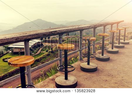 Lonely empty chairs on a deck at sunrise ready for traveler to sit and relax. Travel and Relax concept.