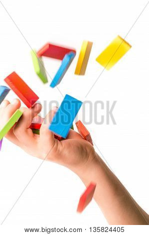 Falling colorful domino into  a hand on white background