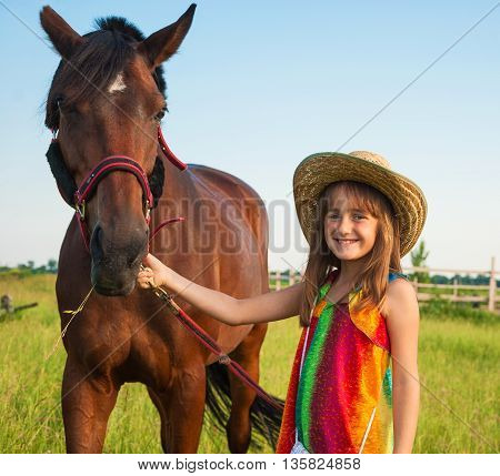 Portrait of a smiling little girl in a cowboy hat with a horse