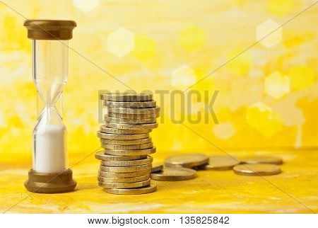 'Time is money' concept: a photo of an hourglass with a pile of coins against a blurred golden yellow background with copyspace