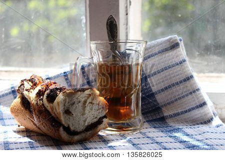 Glass of tea and a bun with poppy seeds