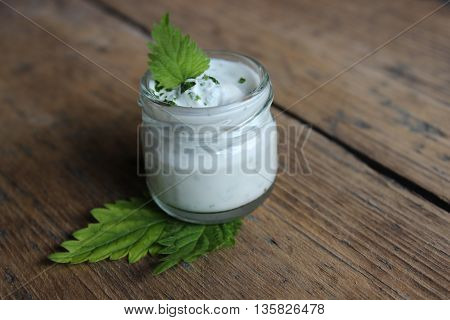 Organic face cream with leaf of nettle on wooden boards