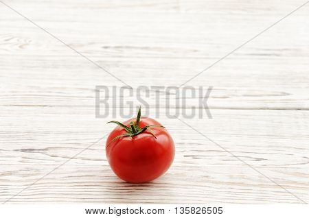 One tomato on white wooden background. Copy space composition.