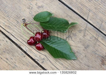Berries cherries on a branch with leaves on a wooden background.