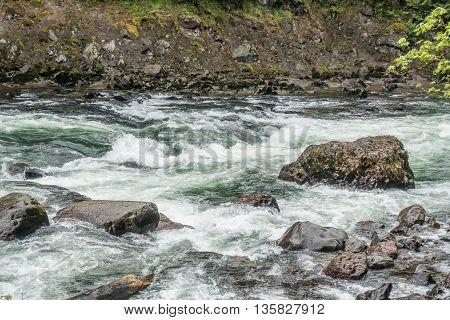 White water rushes past boulders on the Snoqualmie River in Washington State.