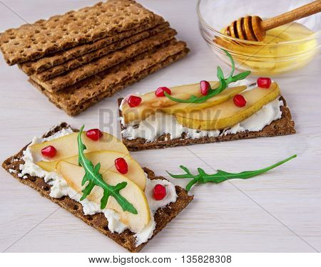Sandwiches with ricotta pear garnet and honey on wooden backdrop