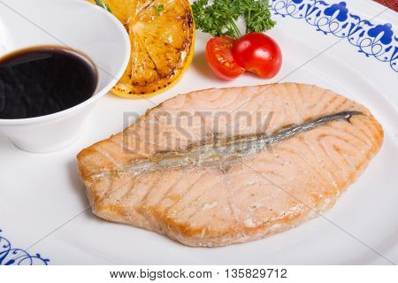 Prepared salmon steak with soy sauce and lemon