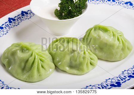 Spinach momo with sour sauce on a white plate