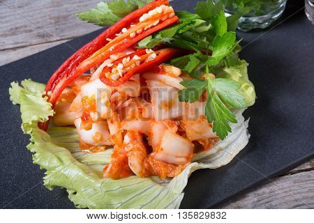 Korean marinated cabbage kimchi dish served with chili pepper
