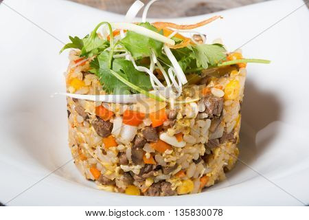 Fried rice with beaf served with herbs on a white plate