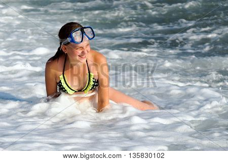 Girl 12 years playing in the oncoming sea wave