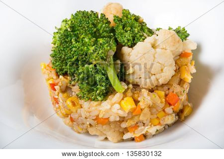 Fried rice with broccoli served on a white plate