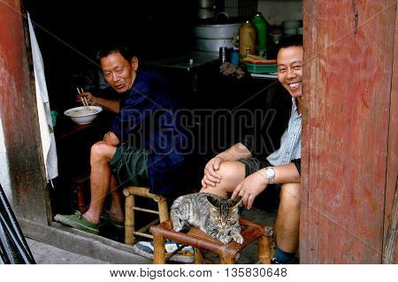 Ao Ping China - September 14 2006: Cat lounging on a bamboo stool with two merchants at their restaurant
