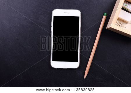 blank screen smartphone and pencil on black background