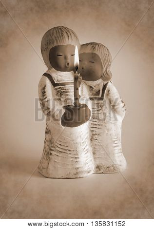 Ceramic candlestick in the form of angels with burning candle - Sepia toned artwork in retro style