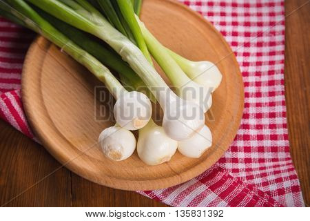some fresh raw ripe green onion on wooden background