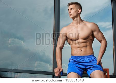 Young man standing strong in the gym and flexing muscles. Muscular athletic bodybuilder fitness model posing after exercises