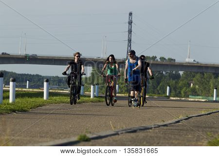 A group of young people a man and a girl riding a bicycle in the city lit by sunlight