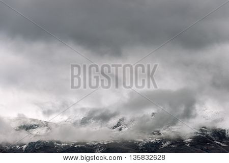 The low clouds over high mountains at a winter day