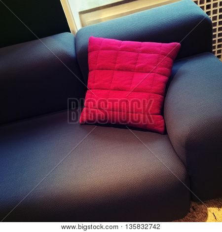 Fashionable textile sofa with bright red cushion. Stylish furniture.