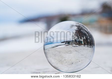 The concept of the world. Crystal ball lies on the riverside promenade in the city in winter. Full ball rotated by 180 degrees.