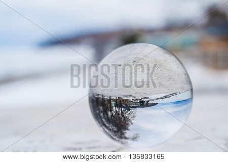 The concept of the world. Crystal ball lies on the riverside promenade in the city in winter.