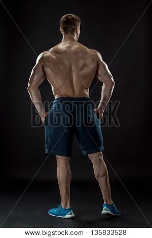 Muscular bodybuilder guy doing posing over black background. He turned his back. full height