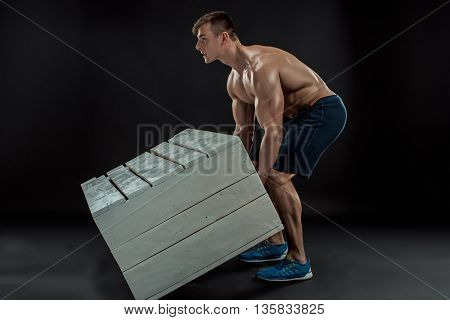 Young Muscular man flipping box. Heavy exercise