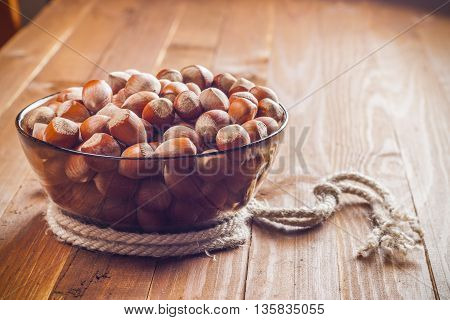 The crude hazelnut in translucent plate with a rope on a table with a wooden background. Healthy food.