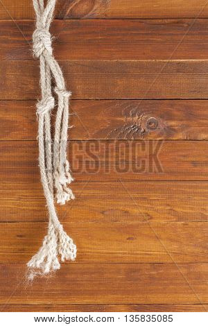 The background texture image of wooden planks and rope. Vertical frame rope frame on the left. Old background.