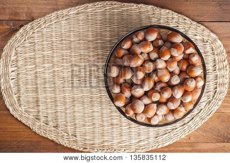 Hazelnuts in wicker plate stands on a napkin with a view from the top. Healthy food.