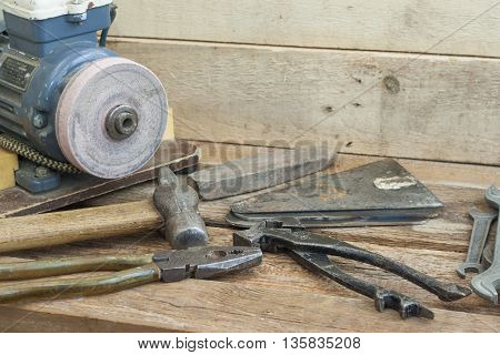 Set of old hand tools lying on a wooden bench. In the background with an electric sharpener. The old shop.