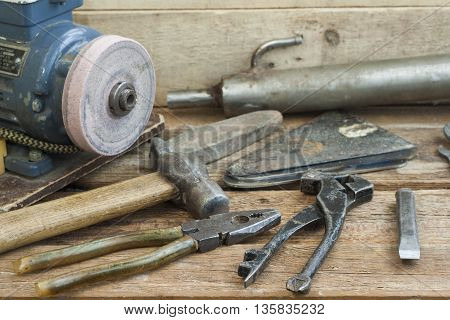 Set of old hand tools lying on a wooden bench. In the background of the winepress with an electric motor and an old pipe. The old shop.