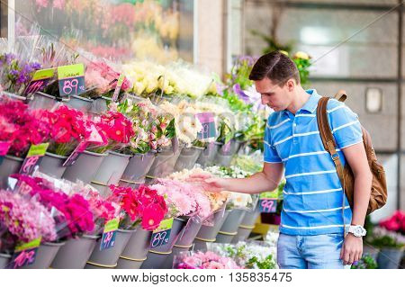 Beautiful young boyselecting flowers at flower market