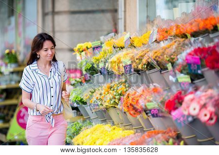 Beautiful young girl selecting flowers at flower market