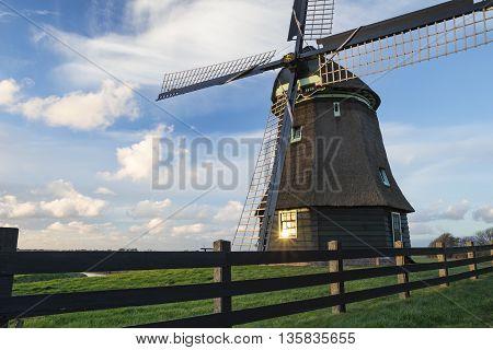 Traditional Dutch windmill under a beautiful cloudy sky