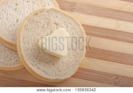Healthy eating concept - piece of round wheat bread with a heart shaped symbol of butter