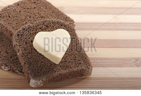 Healthy eating concept - piece of rye bread with a heart shaped symbol of butter