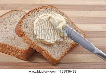 A knife spreading butter on wheat bread