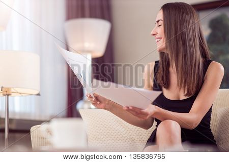 I like my job. Contented young smiling woman holding some papers with diagrams and looking at them while sitting on the couch
