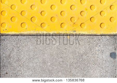 Yellow warning tiles with relief on railway station