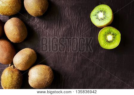 Sweet ripe kiwi fruits on a black stone table